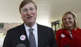 Lt. Gov. Tate Reeves, left, speaks with reporters while his wife Elee Reeves, laughs at his response outside their Flowood, Miss., voting precinct, Tuesday, Nov. 5, 2019. Reeves, the Republican nominee for governor is in one of the state's most hotly contested governor's race since 2003. Voters will also select six other statewide officials and decide on a host of legislative and local offices. (AP Photo/Rogelio V. Solis)