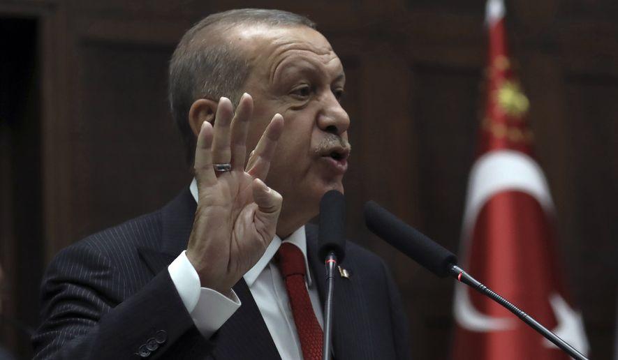 Turkish President Recep Tayyip Erdogan addresses his ruling party legislators at the Parliament, in Ankara. AP Photo/Burhan Ozbilici)