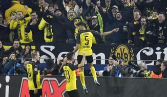 Dortmund's Achraf Hakimi, top, celebrates with his teammates after scoring his side's third goal during the Champions League group F soccer match between Borussia Dortmund and Inter Milan, in Dortmund, Germany, Tuesday, Nov. 5, 2019. (AP Photo/Martin Meissner)