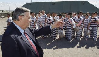 FILE - In this Feb. 4, 2009, file photo, Maricopa County Sheriff Joe Arpaio, left, orders approximately 200 convicted illegal immigrants handcuffed together and moved into a separate area of Tent City, for incarceration until their sentences are served and they are deported to their home countries, in Phoenix. Documents obtained by The Associated Press show a court-appointed investigator concluded that high-ranking managers for former metro Phoenix Sheriff Joe Arpaio disregarded a federal judge's order to halt immigration sweeps targeting Latinos.The investigator also found an internal investigation was whitewashed to shield them from accountability. (AP Photo/Ross D. Franklin, File)