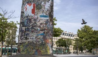 "In this photo taken July 19, 2019 a bird flies past an original piece of the Berlin Wall displayed at the Porte de Versailles, Paris. For nearly three decades, the Berlin Wall encircled West Berlin, built by communist East German authorities ostensibly to protect the country from ""fascists,"" but in reality to prevent their own citizens from fleeing into the democratic half of the divided city, a portal to the rest of the free world. For a barrier meant to prevent travel, chips, chunks and full segments of the 156.4 kilometer-long (97.2 mile-long) reinforced concrete Wall have done a pretty good job themselves getting around Germany and the rest of the world in the past 30 years. (AP Photo/Rafael Yaghobzadeh)"