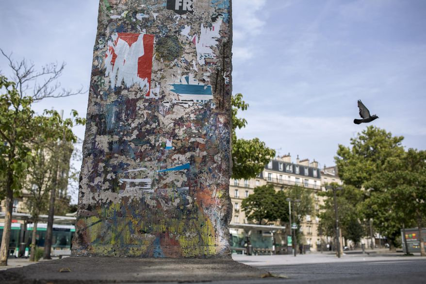 """In this photo taken July 19, 2019 a bird flies past an original piece of the Berlin Wall displayed at the Porte de Versailles, Paris. For nearly three decades, the Berlin Wall encircled West Berlin, built by communist East German authorities ostensibly to protect the country from """"fascists,"""" but in reality to prevent their own citizens from fleeing into the democratic half of the divided city, a portal to the rest of the free world. For a barrier meant to prevent travel, chips, chunks and full segments of the 156.4 kilometer-long (97.2 mile-long) reinforced concrete Wall have done a pretty good job themselves getting around Germany and the rest of the world in the past 30 years. (AP Photo/Rafael Yaghobzadeh)"""