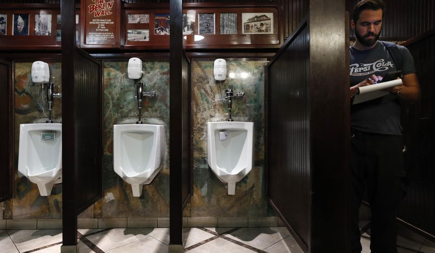 In this Thursday, Sept. 5, 2019, file photo, a man from a television station looks around a bathroom where urinals are mounted on a piece of the Berlin Wall at Main Street Station casino in Las Vegas. (AP Photo/John Locher) ** FIL E **