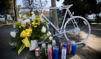 FILE - In a Wednesday, April 11, 2018 file photo, a painted bicycle marks a makeshift memorial for a cyclist who was struck by a hit-and-run motorist in Los Angeles. The National Transportation Safety Boar is recommending that all 50 states enact laws requiring bicyclists to wear helmets to stem an increase in bicycle deaths on U.S. roadways, after a hearing Tuesday, Nov. 5, 2019 on bicycle safety. (AP Photo/Damian Dovarganes, File)