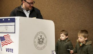 Twins Milo, right, and Amir Klatzkin, 3, watch as their father Barry Klatzkin votes at a polling site in New York, Tuesday, Nov. 5, 2019. New York's first election with early voting is reaching its conclusion as people across the state cast ballots in county and municipal races. With no federal or statewide contests on the ballot Tuesday, turnout is expected to be low, but this year's contests are serving as a rehearsal for next year's blockbuster presidential race. (AP Photo/Seth Wenig)