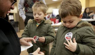 "Twins Amir, right, and Milo Klatzkin, 3, put on their ""I Voted"" stickers after their father Barry Klatzkin, left, voted at a polling site in New York, Tuesday, Nov. 5, 2019. New York's first election with early voting is reaching its conclusion as people across the state cast ballots in county and municipal races. With no federal or statewide contests on the ballot Tuesday, turnout is expected to be low, but this year's contests are serving as a rehearsal for next year's blockbuster presidential race. (AP Photo/Seth Wenig)"