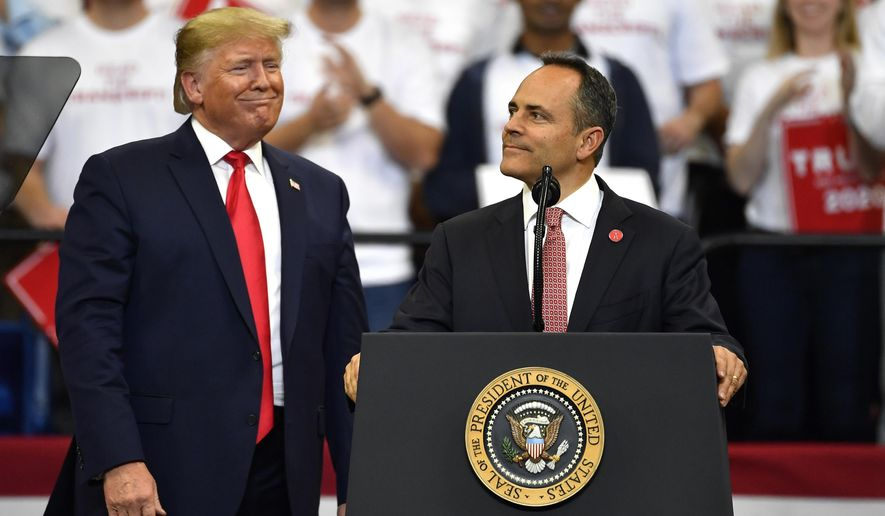 Kentucky Gov. Matt Bevin, right, looks out at the crowd as President Donald Trump watches during a campaign rally in Lexington, Ky., Monday, Nov. 4, 2019. (AP Photo/Timothy D. Easley)