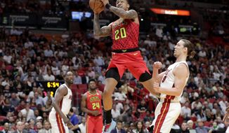 Atlanta Hawks forward John Collins (20) drives to the basket past Miami Heat forward Kelly Olynyk during the first half of an NBA basketball game Tuesday, Oct. 29, 2019, in Miami. (AP Photo/Lynne Sladky)