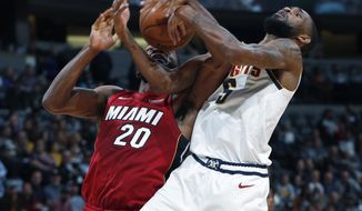 Denver Nuggets forward Will Barton, right, fights for control of a rebound with Miami Heat forward Justise Winslow in the first half of an NBA basketball game Tuesday, Nov. 5, 2019, in Denver. (AP Photo/David Zalubowski)