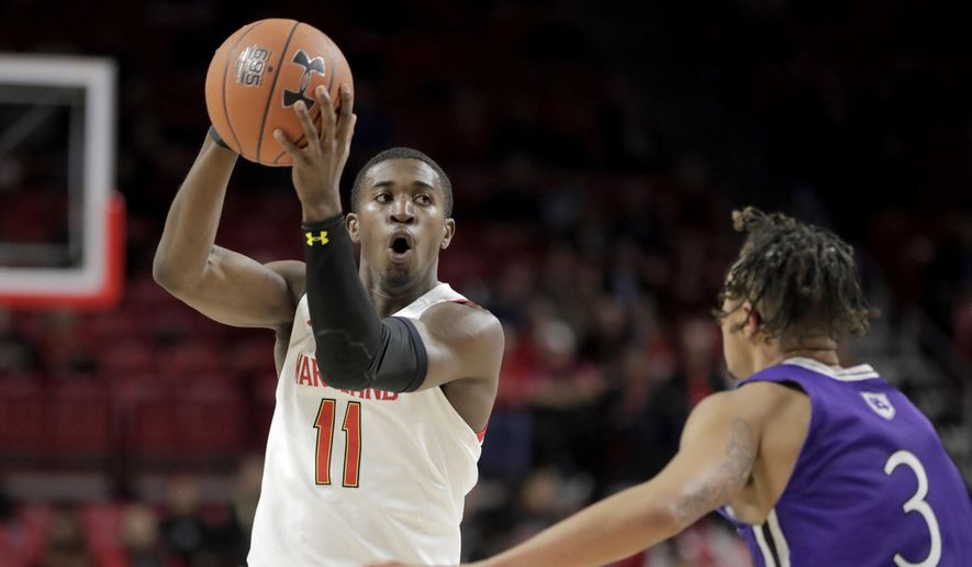 Maryland guard Darryl Morsell (11) looks to pass against Holy Cross guard Drew Lowder (3) during the first half of an NCAA college basketball game, Tuesday, Nov. 5, 2019, in College Park, Md. (AP Photo/Julio Cortez)