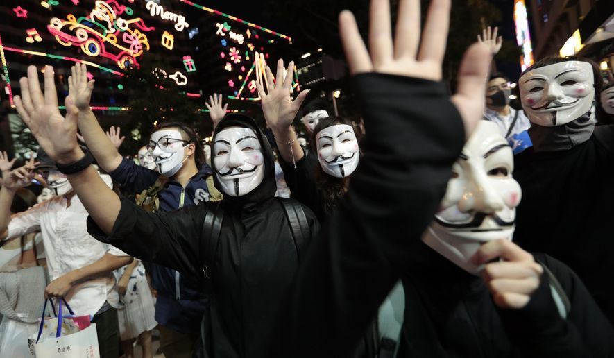 Protesters in Guy Fawkes masks raise their hands as they chant slogans during a rally in Hong Kong, Tuesday, Nov. 5, 2019. Hong Kong's embattled leader, Carrie Lam, said Tuesday that she has received the backing of Chinese President Xi Jinping in her handling of five months of anti-government protests that have rocked the semi-autonomous Chinese territory. (AP Photo/Dita Alangkara)