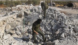 In this Oct. 27, 2019, file photo, people look at a destroyed house near the village of Barisha, in Idlib province, Syria, after an operation by the U.S. military that targeted Abu Bakr al-Baghdadi, the shadowy leader of the Islamic State group. (AP Photo/Ghaith Alsayed, File)