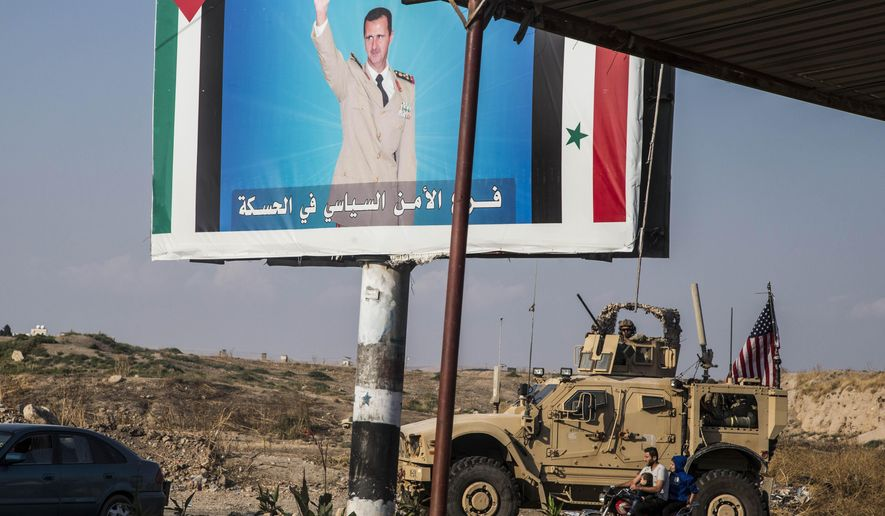 U.S. military convoy drives the he town of Qamishli, north Syria, by a poster showing Syrain President Bashar Aassad Saturday, Oct. 26. 2019. A U.S. convoy of over a dozen vehicles was spotted driving south of the northeastern city of Qamishli, likely heading to the oil-rich Deir el-Zour area where there are oil fields, or possibly to another base nearby. The Syrian Observatory for Human Rights, a war monitor, also reported the convoy, saying it arrived earlier from Iraq. (AP Photo/Baderkhan Ahmad)