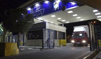 A truck containing cylinder of uranium hexafluoride gas leaves Ahmadi Roshan uranium enrichment facility in Natanz to Fordo nuclear facility in the early morning on Wednesday, for the purpose of injecting the gas into Fordo centrifuges. (Atomic Energy Organization of Iran via AP)