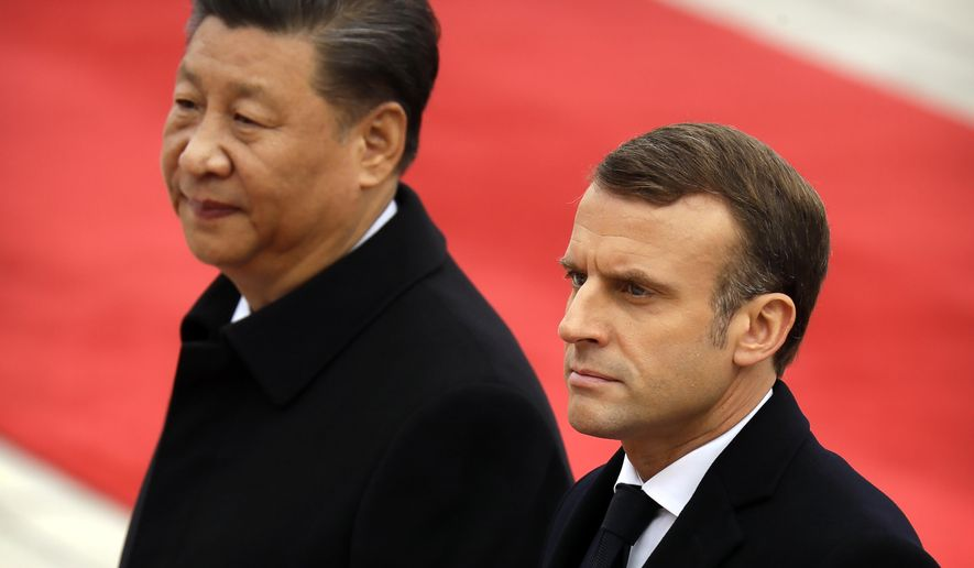 Chinese President Xi Jinping, left, and French President Emmanuel Macron walk together during a welcome ceremony at the Great Hall of the People in Beijing, Wednesday, Nov. 6, 2019. (AP Photo/Mark Schiefelbein)