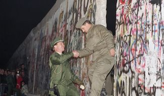 FILE - In this Sunday Nov. 12, 1989 file photo, West German policeman, left, gives a helping hand to an East German border guard who climbs through a gap of the Berlin Wall when East Germany opened another passage at Potsdamer Platz in Berlin. (AP Photo/Thomas Kienzle)