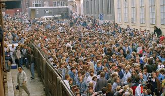 FILE - In this Wednesday, Oct. 4, 1989 file photo, a crowd of about 10,000 East German refugees throng in the street outside the West German embassy in Prague, Czech Republic, before they are allowed to board busses to take them to special trains bound for West Germany. (AP Photo/Dieter Endlicher, File)
