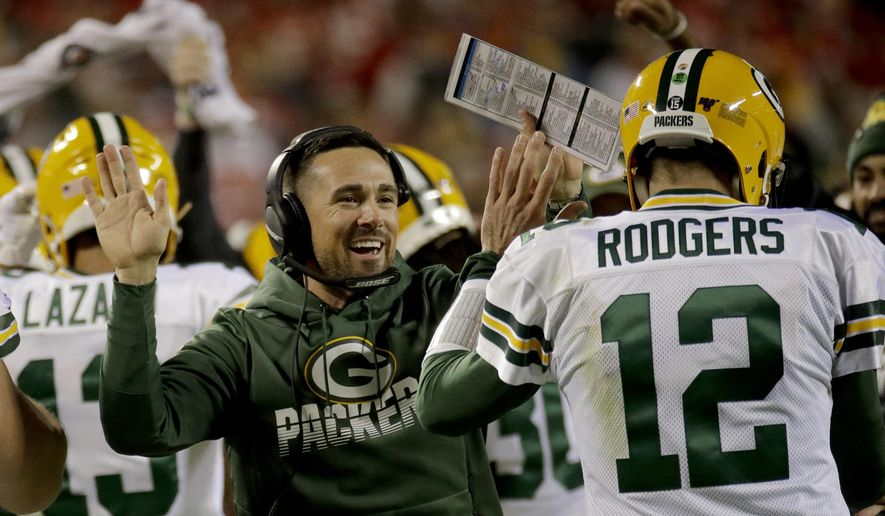 FILE - In this Sunday, Oct. 27, 2019, file photo, Green Bay Packers head coach Matt LaFleur celebrates with quarterback Aaron Rodgers (12) after a touchdown during the first half of an NFL football game against the Kansas City Chiefs, in Kansas City, Mo. Being a rookie head coach in the NFL is challenging enough, and also calling plays for the offense only increases the difficulty. Having Rodgers has helped ease the growing pains for LaFleur. (AP Photo/Charlie Riedel, File)