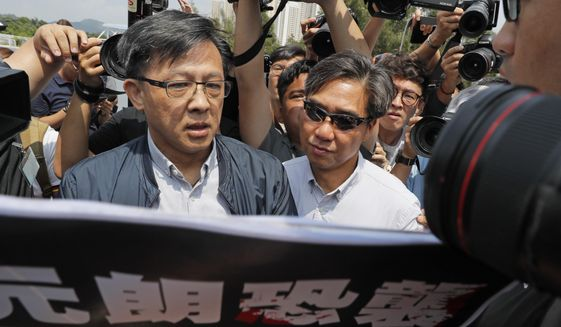 In this Aug. 12, 2019, photo, pro-Beijing lawmaker Junius Ho, left, attends a demonstration of an anti-riot vehicle equipped with water cannon at the Police Tactical Unit Headquarters in Hong Kong. Hong Kong police say an anti-government supporter stabbed and wounded the pro-Beijing lawmaker who was campaigning for local elections. The government condemned the attack on Wednesday, Nov. 6, 2019 against Ho, a hate figure for protesters, and said police arrested the assailant. (AP Photo/Kin Cheung)