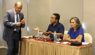 Cambodia's ambassador to Indonesia Hor Nambora, left, interrupts the press conference held by Mu Sochua, right, Vice President of the Cambodia National Rescue Party (CNRP) and Executive Director Kurawal Foundation Darnawan Triwibowo, center, in Jakarta Indonesia, Wednesday, Nov. 6, 2019. The press conference was held by the Cambodian opposition group to discuss plans for its exiled leaders, including Sam Rainsy, to return to their homeland against the government's wishes. (AP Photo/Achmad Ibrahim)