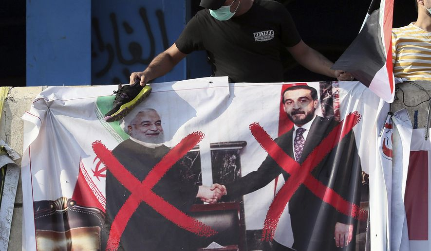 A poster of Iraq Parliament Speaker Mohammed al-Halbousi, right, and Iran President Hassan Rouhani, left, hang on a building near Tahrir Square, during ongoing protests in Baghdad, Iraq, Wednesday, Nov. 6, 2019. (AP Photo/Hadi Mizban)