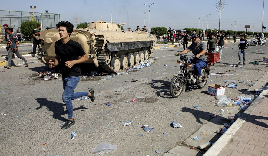 Anti-government protesters block the port of Umm Qasr while Iraqi security forces try to reopen the key oil terminal on the Persian Gulf, Iraq, Tuesday, Nov. 5, 2019. (AP Photo/Nabil al-Jourani)