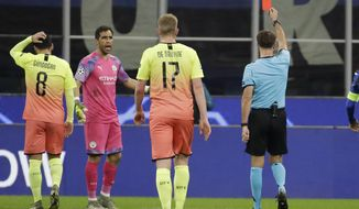 Referee Aleksei Kulbakov, right, gives a red card to Manchester City's goalkeeper Claudio Bravo, second from left, during the Champions League group C soccer match between Atalanta and Manchester City at the San Siro stadium in Milan, Italy, Wednesday, Nov. 6, 2019. (AP Photo/Luca Bruno)