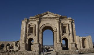 FILE - In this Nov. 13, 2015, file photo, tourists pass through the Arch of Hadrian, built during the Roman Empire, and the South Gate of the well preserved Ancient Roman city of Gerasa, in the city of Jerash, Jordan. Jordanian officials say an attacker has stabbed a number of tourists and their tour guide at a popular archaeological site in northern Jordan. The wounded were taken to a hospital and the attacker was arrested. (AP Photo/Nasser Nasser, FIle)