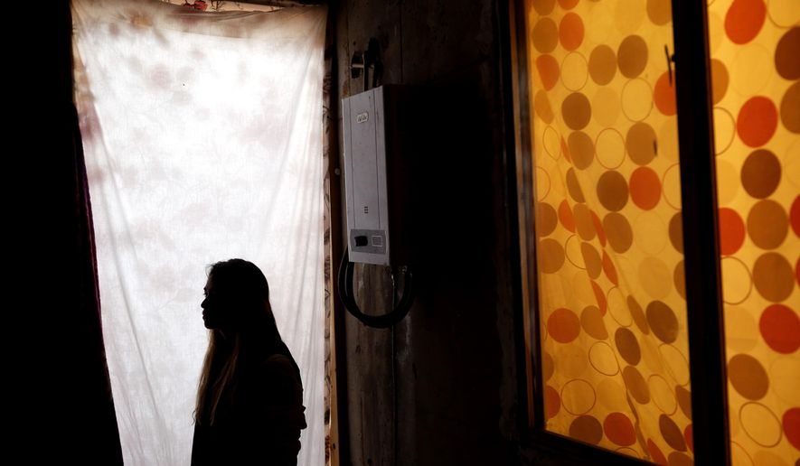 "In this Tuesday, Nov. 5, 2019, photo, Lizbeth poses for a portrait in a relative's home in Tijuana, Mexico. Lizbeth, a Salvadoran woman seeking asylum in the United States, never thought she would be returned to Mexico to wait for the outcome of her case, after suffering multiple assaults, and being kidnapped into prostitution on her journey through Mexico. Critics of the Trump administration's ""Migrant Protection Protocols"" policy, say it denies asylum seekers fair and humane treatment, largely by forcing them to wait in a country plagued by large pockets of drug-fueled violence, demonstrated this week by the slaughter near the U.S. border of several children and women. (AP Photo/Gregory Bull)"