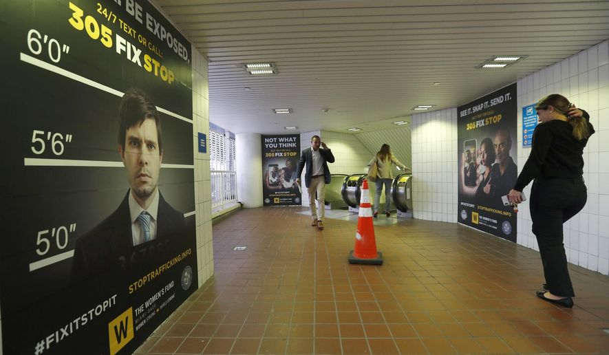 Pedestrians pass large posters aimed at curbing sex trafficking, Wednesday, Nov. 6, 2019, at the Metromover Knight Center Station in Miami. Authorities in Miami are launching the initiative in the events surrounding February's Super Bowl. (AP Photo/Wilfredo Lee)
