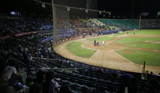 The stadium is partially empty during the opening winter season game between Los Leones de Caracas and Los Tigres de Aragua in Caracas, Venezuela, Tuesday, Nov. 5, 2019. A deepening crisis has left her nation in shambles, and a recent curve ball from the Trump administration has prevented big league players in the MLB from taking the field, stripping away star-power that fans have come to expect over decades. (AP Photo/Ariana Cubillos)