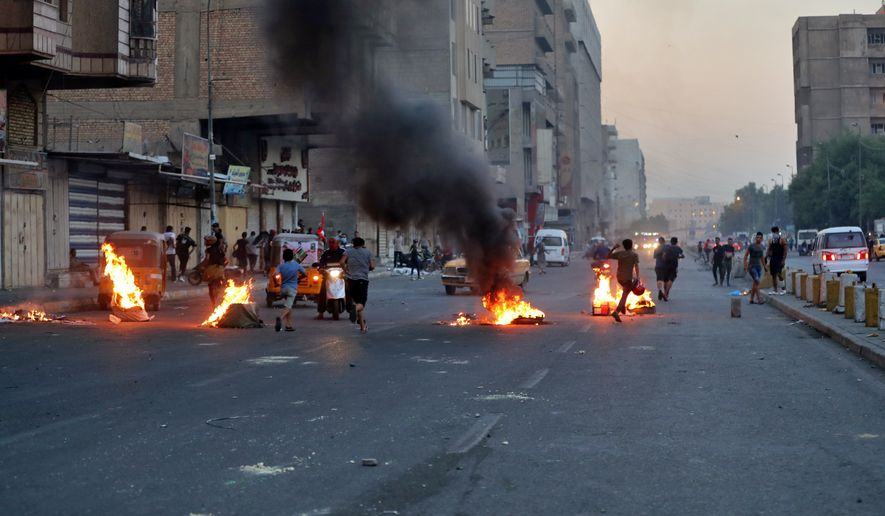 Anti-government protesters set fire and close streets during ongoing protests in Baghdad, Iraq, Thursday, Nov. 7, 2019. Iraqi security forces opened fire on Thursday, killing several protesters as they were trying to remove barriers blocking their march in central Baghdad, while in the south, demonstrators forced the closing of the country's main port, hours after services had resumed following days of closure, officials said. (AP Photo/Khalid Mohammed)