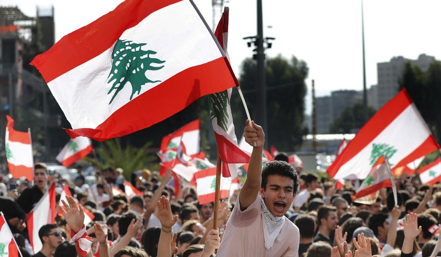Student protesters wave national flags as they protest against the government in front of the education ministry in Beirut, Lebanon, Thursday, Nov. 7, 2019. Lebanese protesters are rallying outside state institutions and ministries to keep up the pressure on officials to form a new government to deal with the country's economic crisis. (AP Photo/Hussein Malla)
