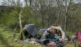 FILE - In this Wednesday, Feb. 13, 2019 file photo, from left, Terry Flakes, Kim Smith, and Tracy Botlinger have lunch at their camp in south Austin, Texas. Texas' Republican governor is creating a homeless campsite on state land amid an escalating battle with liberal leaders in the state capital over people living on the streets. National advocates for the homeless said Thursday, Nov. 7, 2019 they couldn't recall another state making such a move, which follows Gov. Greg Abbott's months-long feud with Austin on Twitter. The encampment site covers 5 acres on the outskirts of downtown. (James Gregg/Austin American-Statesman via AP, File)
