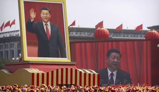 FILE - In this Oct. 1, 2019, file photo, participants cheer beneath a large portrait of Chinese President Xi Jinping during a parade to commemorate the 70th anniversary of the founding of Communist China in Beijing. (AP Photo/Mark Schiefelbein, File)