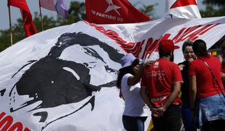Workers' Party members gather to show support for Brazil's jailed, former President Luiz Inacio Lula da Silva, outside the Supreme Court in Brasilia, Brazil, Thursday, Nov. 7, 2019. Judges are debating whether a defendant is to begin serving his sentence after a conviction has been reached by the first appellate court, which could affect cases like that of Da Silva. (AP Photo/Eraldo Peres)