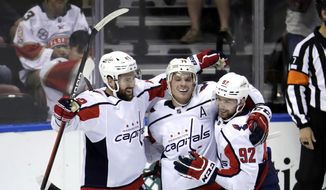 Washington Capitals right wing Tom Wilson, left, celebrates with defenseman John Carlson, center, and center Evgeny Kuznetsov (92) after scoring a goal during overtime of an an NHL hockey game against the Florida Panthers, Thursday, Nov. 7, 2019, in Sunrise, Fla. (AP Photo/Lynne Sladky)