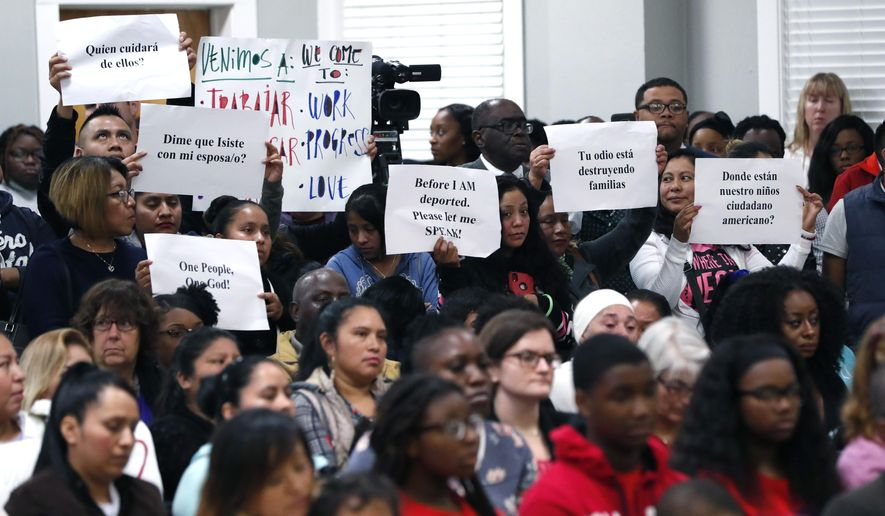 About 50 immigrant workers, their families and supporters hold signs calling attention to the plight of the almost 700 poultry processing plant workers that were arrested in August, during a ICE raid, at a House Homeland Security Committee field hearing at Tougaloo College in Jackson, Miss., Thursday, Nov. 7, 2019. (AP Photo/Rogelio V. Solis) **FILE**