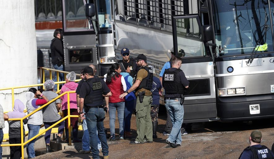 In this Wednesday, Aug. 7, 2019, photo, handcuffed workers are escorted into a bus for transportation to a processing center following a raid by U.S. immigration officials at a Koch Foods Inc., plant in Morton, Miss. Three months after immigration agents arrested 680 Latino workers in a massive workplace sting at seven Mississippi chicken processing plants, a congressional committee plans a hearing into the raids and their effects, Thursday, Nov. 7, in Jackson, Miss. (AP Photo/Rogelio V. Solis) **FILE**