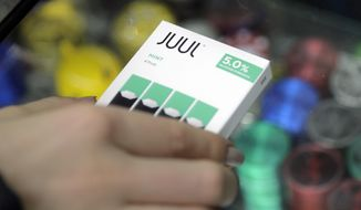 In this Dec. 20, 2018, file photo a woman buys refills for her Juul at a smoke shop in New York. The e-cigarette maker Juul Labs said Thursday, Nov. 7, 2019, that it will halt sales of its best-selling mint-flavored vaping pods. (AP Photo/Seth Wenig, File) **FILE**