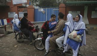 Pakistani students stand outside their school which is closed due to poor air quality in Lahore, Pakistan, Thursday, Nov. 7, 2019. The government ordered all schools in the eastern Punjab capital of Lahore closed because of the poor air quality. A thick smog hung over the city of 11 million people on Thursday. (AP Photo/K.M. Chaudary)