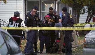 In this Wednesday, Nov. 6, 2019 photo, St. Paul Police comfort mourners at the scene where a teenage boy was shot dead on Annapolis Street East in St. Paul, Minn. (Shari L. Gross/Star Tribune via AP)