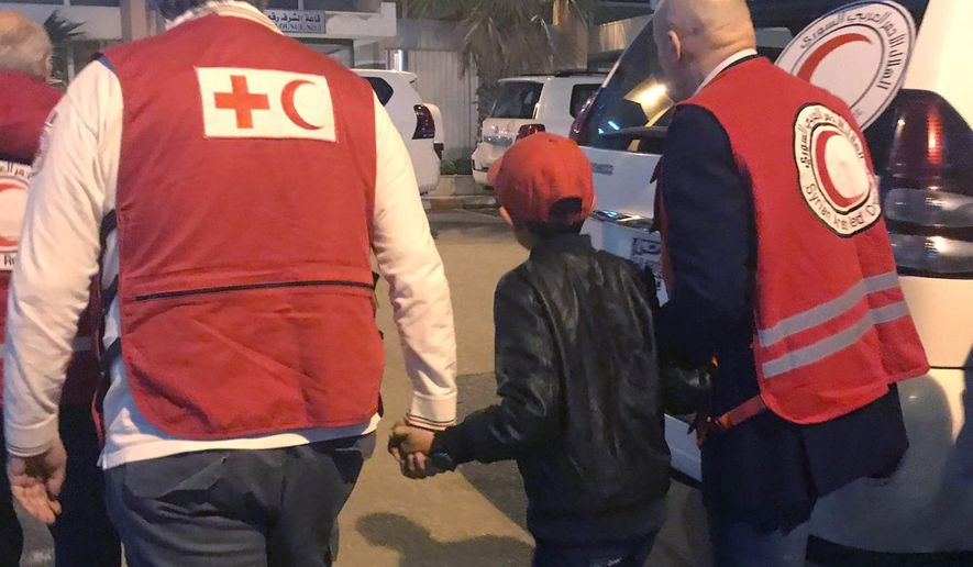 In this photo taken Wednesday, Nov. 6, 2019, Alvin, an 11-year-old Albanian boy who was taken to Syria by his mother when she joined the Islamic State group, is accompanied to Damascus airport by Red Cross and Red Crescent officials, after he was freed from a crowded detention camp. The boy, who found himself with no family in the al-Hol camp run by Kurdish forces in northeastern Syria after his mother and siblings died amid fighting, is heading home, to Italy, where his father lives. (International Federation of Red Cross and Red Crescent photo via AP)