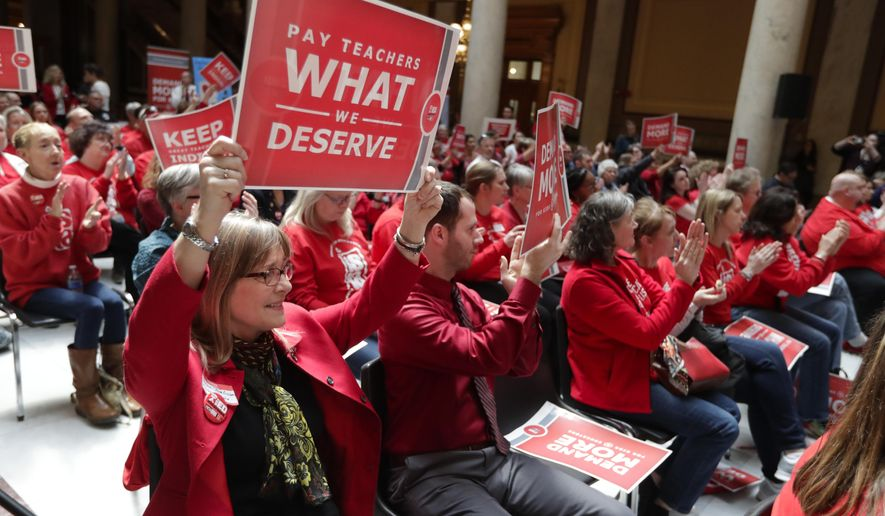 FILE - In this April 16, 2019, file photo, teachers cheer during a rally at at the Statehouse in Indianapolis. School days are being called off for tens of thousands of Indiana students as their teachers make plans for attending a union-organized Statehouse rally. Some school district officials say so many teachers requested personal time off for the Nov. 19 rally that they wouldn't be able to find enough substitute teachers to cover classrooms. A state teachers union leader says at least 4,000 teachers have registered for the rally. (AP Photo/Michael Conroy File)
