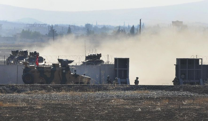 In this photo taken from the outskirts of the village of Mert Ismail near the town of Suruc, southeastern Turkey, Turkish army vehicles return to Tirley from Syrian after conducting a joint patrol with Russian forces, Tuesday, Nov. 5, 2019. Turkey and Russia launched joint patrols for the second time in northeastern Syria, under a deal that halted a Turkish offensive against Syrian Kurdish fighters who were forced to withdraw from the border area following Ankara's incursion. (AP Photo/Mehmet Guzel)