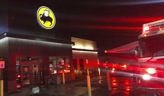 Emergency crews at the Buffalo Wild Wings restaurant in Burlington, Mass. Thursday night, Nov. 7, 2019. Massachusetts authorities say an employee of the restaurant has died and others have been hospitalized following a chemical mixture at the restaurant. (John Guilfoil via AP)