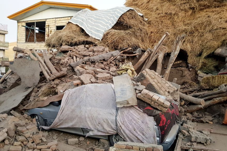 A car lays smashed by debris from an earthquake in Varankesh village in Eastern Azerbaijan province, some 250 miles (400 kilometers) northwest of the capital Tehran, Iran, Friday, Nov. 8, 2019. The temblor struck Tark county in Iran's Eastern Azerbaijan province early Friday. (Mohammad Zinali/Tasnim News Agency via AP)