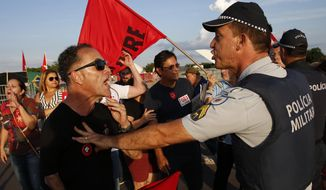 Police attempt to defuse a situation between supporters of jailed former President Luiz Inacio Lula da Silva and President Jair Bolsonaro, as both groups keep vigil outside the Supreme Court in Brasilia, Brazil, Thursday, Nov. 7, 2019. (AP Photo/Eraldo Peres)
