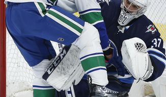 Winnipeg Jets goaltender Connor Hellebuyck (37) and Vancouver Canucks' Brandon Sutter (20) get tangled up during the first period of an NHL hockey game, Friday, Nov. 8, 2019 in Winnipeg, Manitoba. (John Woods/Canadian Press via AP)