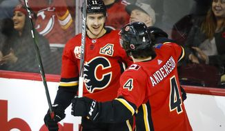 Calgary Flames' Mikael Backlund, left, celebrates his goal with Rasmus Andersson during the second period of an NHL hockey game against the New Jersey Devils on Thursday, Nov. 7, 2019, in Calgary, Alberta. (Jeff McIntosh/The Canadian Press via AP)